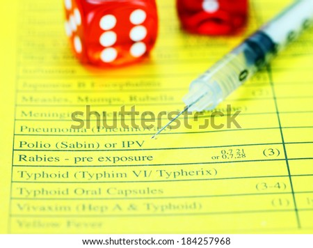 Two red translucent dice placed on a vaccination passport with a loaded syringe next to it, asking the question will you gamble by not having the proper vaccinations! - stock photo