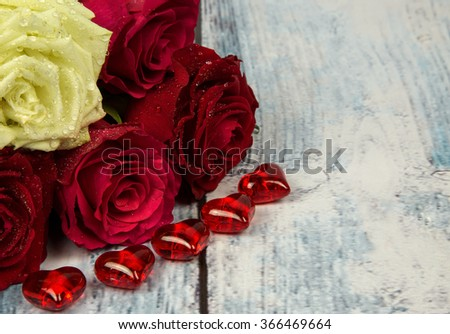 Two red, two maroon and one white rose ,valentines hearts with dew drops on  background wooden plank  vintage effect and space for additional text .Horizontal view.on the right side. Horizontal view.