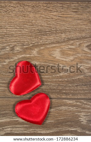 Two red valentines day hearts on wooden background