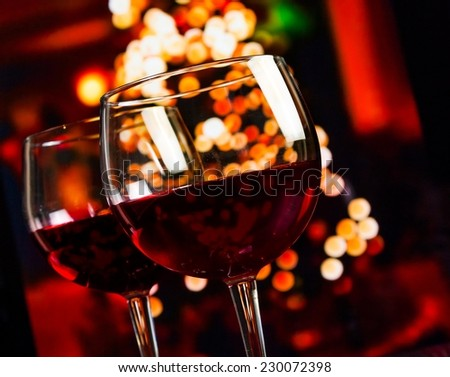 two red wine glass against christmas lights decoration background, christmas atmosphere - stock photo