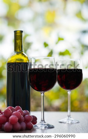 two red wine glass and bottle on rustic wood surface with red grapes - stock photo