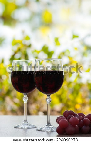 two red wine glass on rustic wood surface with red grapes