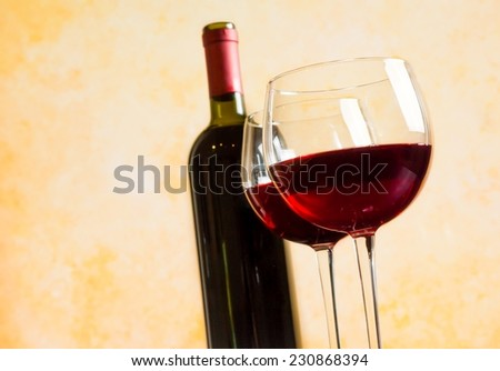 two red wine glasses against old wall background, festive concept - stock photo