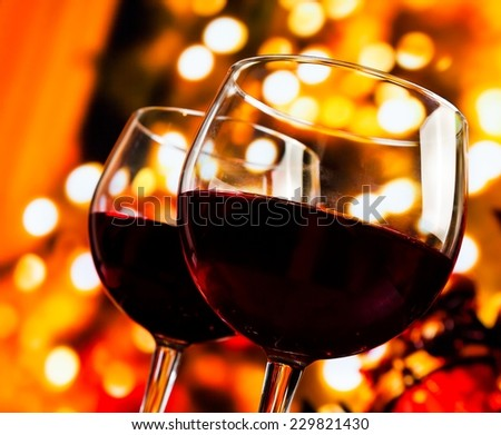 two red wine glasses against tree of bokeh lights background, christmas atmosphere - stock photo