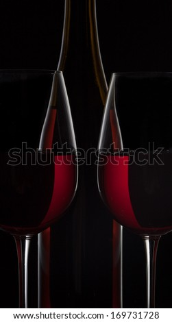 Two red wine glasses and wine bottle silhouettes on black background
