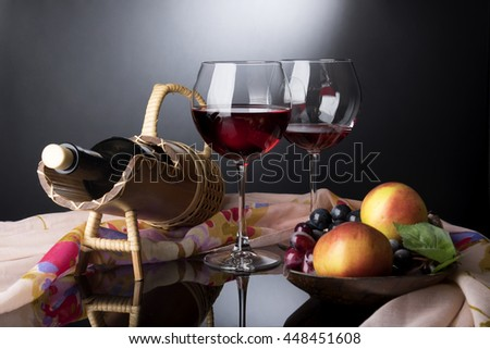 Two red wine glasses, bottle in straw prop and wooden plate with vines and apples situated on black mirror tablecovered by rosy cloth - stock photo