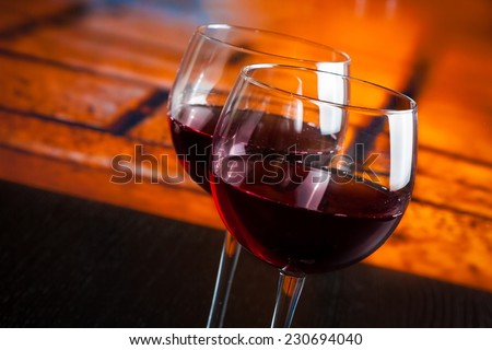 two red wine glasses on wood table with warm atmosphere background, festive and fun concept - stock photo