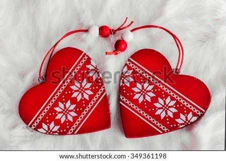 two red wooden heart with Scandinavian ornaments on a white fur - stock photo