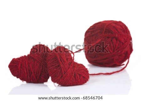 Two red woolen hearts connected in one knot - stock photo