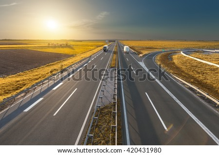 Two reefer modern trucks driving towards the sun. Fast blurred motion driving on the freeway in beautiful autumn scenery. Freight scene on the motorway near Belgrade, Serbia. - stock photo