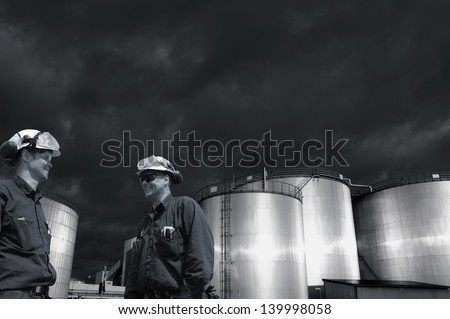 two refinery workers with large industrial fuel tanks - stock photo
