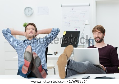 Two relaxed confident young business partners sure of their own success sitting with their feet up on the desk and complacent smiles - stock photo