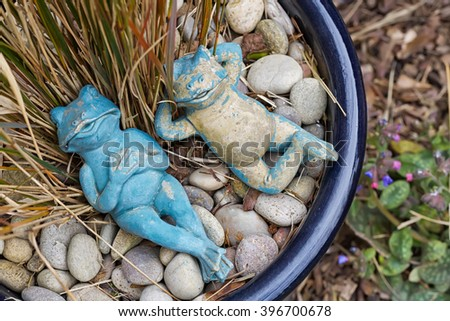 Two relaxing blue and beige garden frogs figures lying in a plant pot as a garden decoration, artificial toy - stock photo