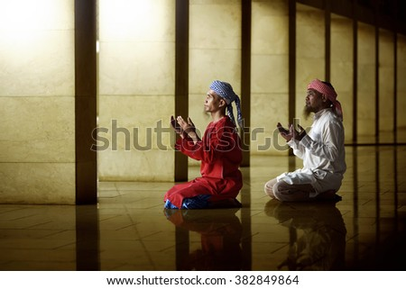 Two religious muslim man praying together inside the mosque - stock photo