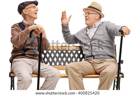 Two retired elderly people sitting on a bench and laughing isolated on white background - stock photo