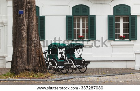 Two retro cyclo parking in front of a five stars French architecture in Hanoi, Vietnam. - stock photo
