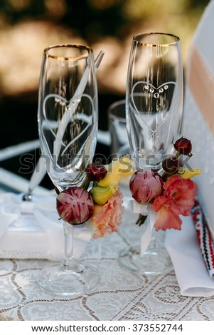 Two rich blank decorated wedding glasses with sprig of delicate beige roses on the table with a white tablecloth. - stock photo
