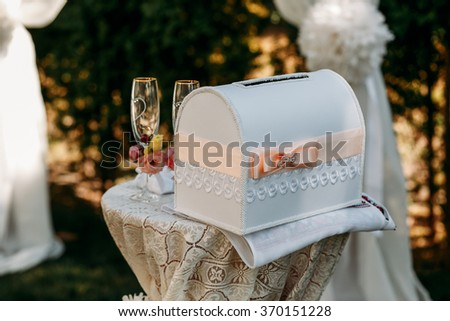 Two rich decorated wedding glasses on the table with box for congratulations - stock photo