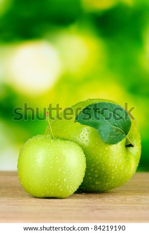 Two ripe apples on table outdoors - stock photo