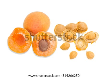 Two ripe apricot, one of which is cut in half and several apricot kernels closeup on a light background. Isolation. - stock photo