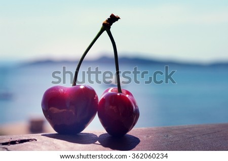 Two ripe berries of sweet cherry against the sea. Romantic couple. Two juicy cherries in the form of heart - stock photo