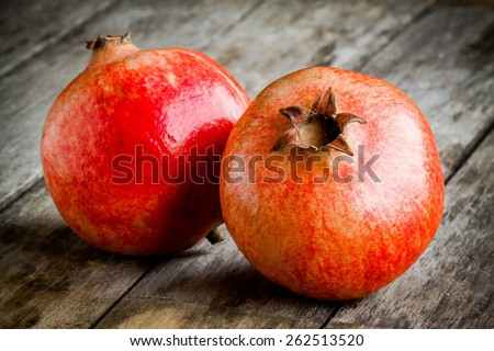 two ripe pomegranate on a wooden rustic background - stock photo