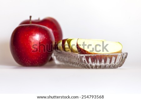 Two ripe red apples and segments of apple on a plate - stock photo