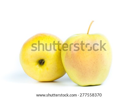 two ripe yellow apples lie under different corners to the camera - stock photo