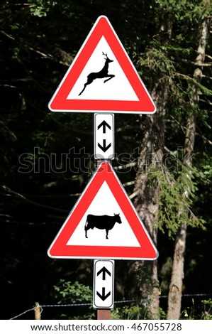 two road signs near the forest caution crossing animals cow and deer