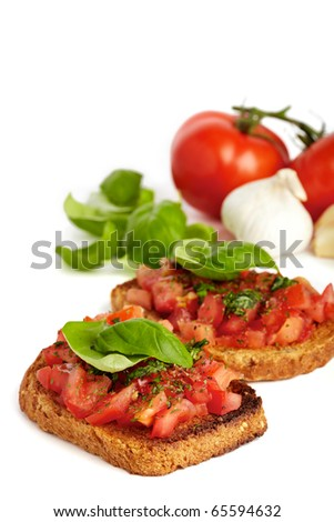 Two roasted breads with tomato, garlic and basil, isolated on white - stock photo