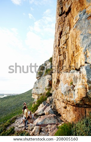 Two rock climbers looking up at a steep mountain with their climbing equipment with copyspace - stock photo