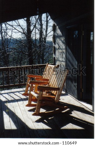 Two rocking chairs on the deck of a cabin in the Smokey Mountains