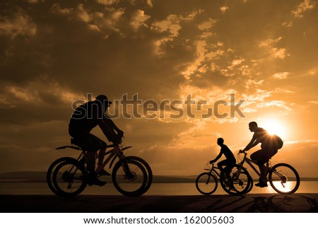 two romantic couples cyclists ride towards each other silhouette in sunrise   against sun set cloudy sky and sea shore background Space for inscription