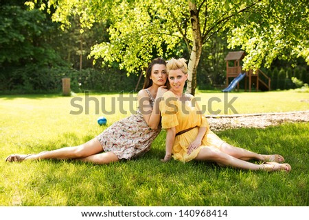 Two romantic girl sitting on flower meadow - stock photo