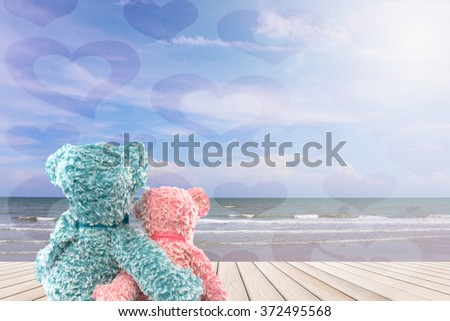 two romantic teddy bear sitting on wood platform by the ocean with beautiful blue sky and hearts all around - Valentine romance love concept - stock photo