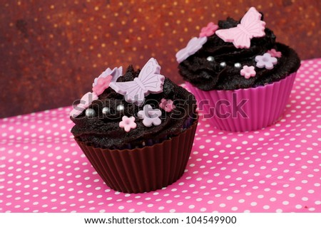 Two romantic wedding cupcake with flowers and butterfly