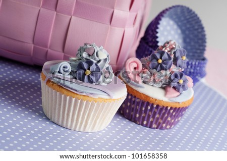 two romantic wedding cupcakes in lilac pink setting - stock photo