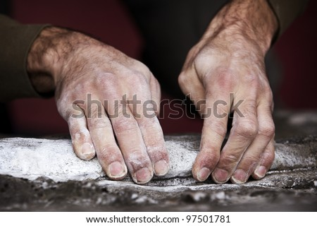 Two rough and dirty hands grip a rock ledge during a bouldering outing. Hands are covered in chalk and grit. - stock photo