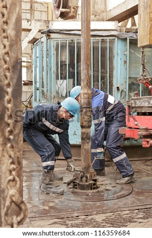 Two roughnecks do the equipment for fixing of rig pipe - stock photo