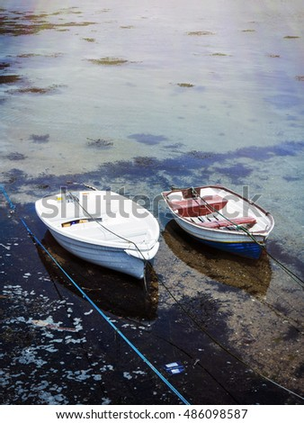 Two row boats tied up in St. Ives harbor with lighting effect.
