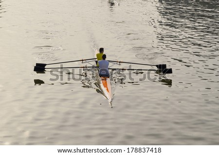 Two rowers in a river viewed from backside - stock photo