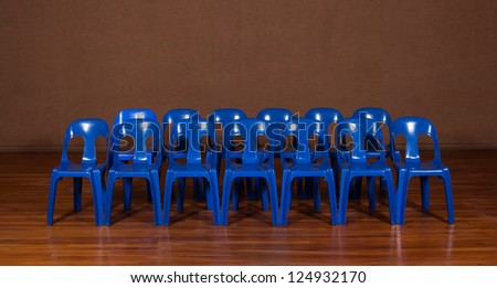 Two rows of blue plastic chairs. - stock photo