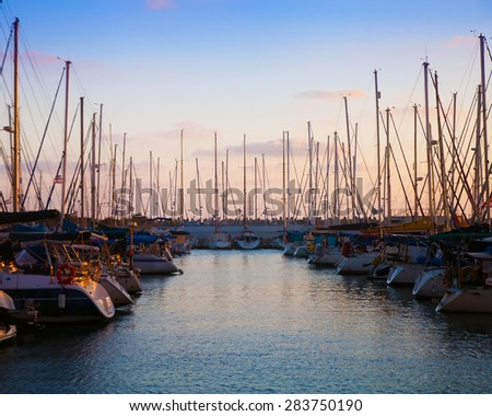 Two rows of boats lying at pier in the evening against sunset skies (sunset dusk lighting) - stock photo
