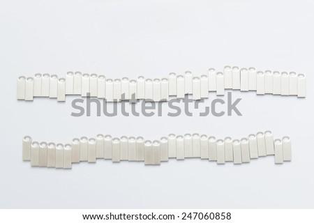 two rows of metal usb sticks on white - stock photo