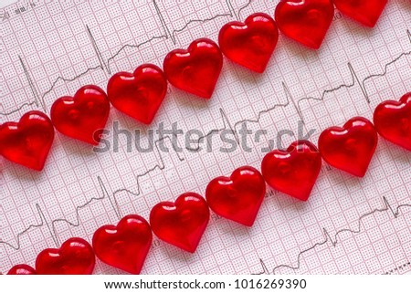 Two rows of red hearts on the background of the electrocardiogram (ECG). Heart rate.