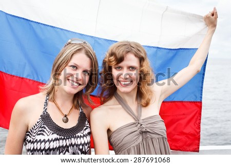 Two Russian beautiful young females are standing under flag of Russia