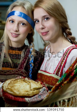 Two russian girls in national costumes with pancakes - stock photo