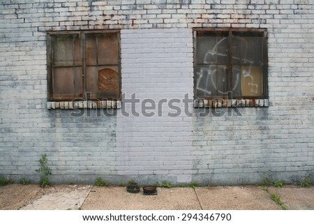 Two Rusted Metal Window Frames On Side Of Brick Building