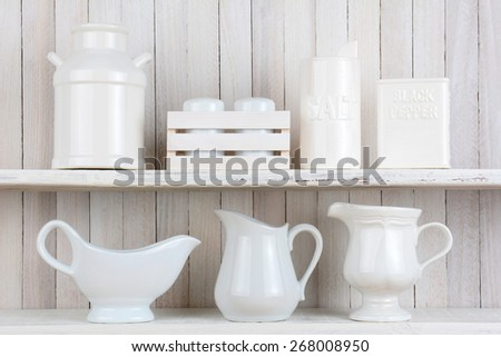 Two rustic white wood kitchen shelves with all white accessories. Items include, Salt and pepper shakers, pitchers, gravy boat and ceramic milk can. Horizontal format. - stock photo