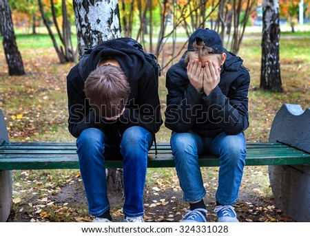 Two Sad Boys on the Bench in the Autumn Park - stock photo
